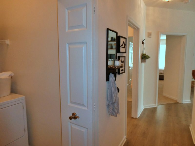 This image shows an expansive view of the Premium Apartment Feature, especially the full-size washer and dryer that will make every resident's home more accessible and comfy to live in. Showing the washer and dryer room and its passageway through the rooms beside it.